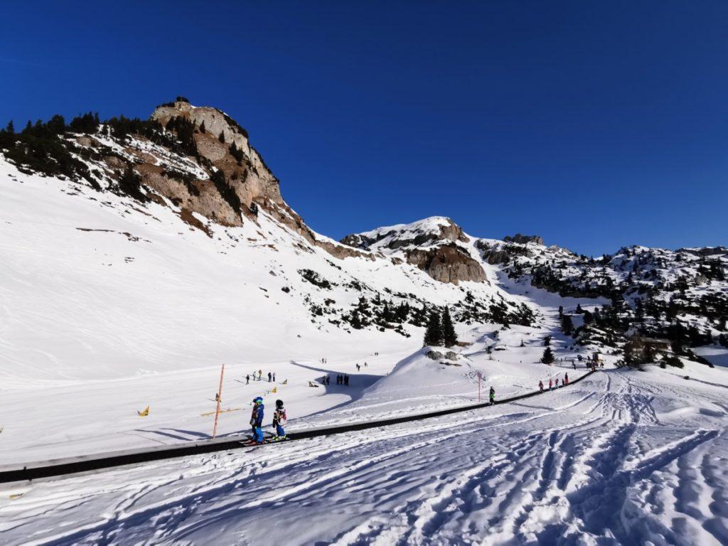 Rofan Winterwanderung - die Kinder fahren auf dem ewig langen Förderband mit Ski oder Schlitten